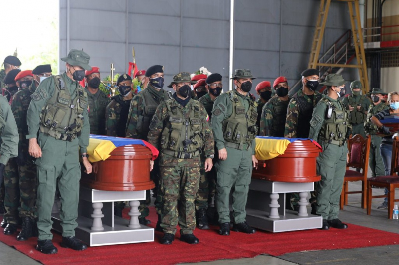 Members of the Venezuelan military stand beside two coffins